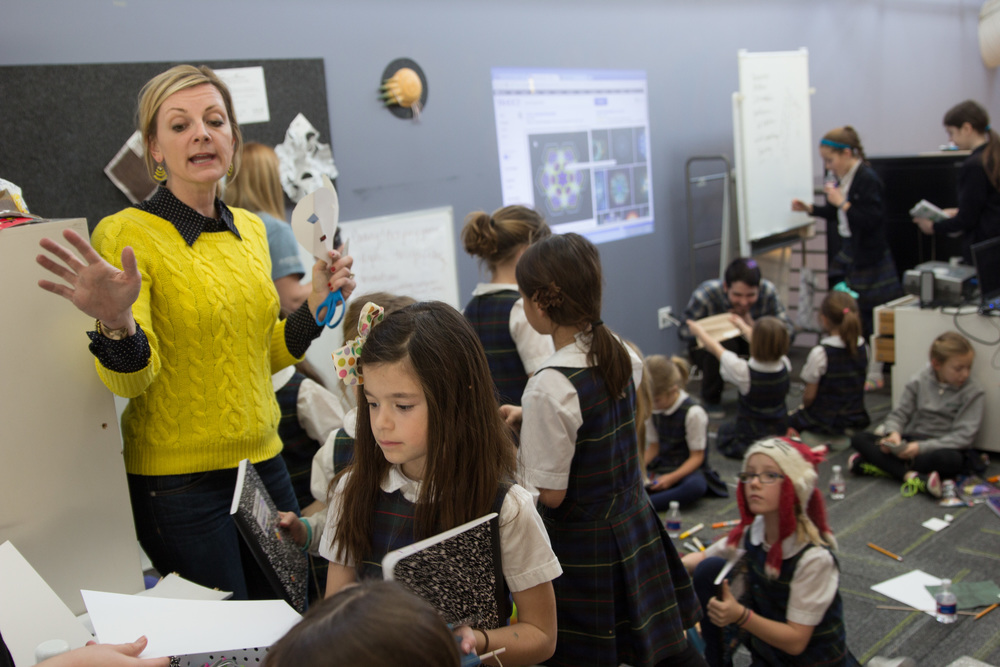 Mandi Sonnenberg, Ed.D., associate professor of education at Rockhurst University, leads an activity during the STEAM camp for girls at Gould Evans STEAM Studio in Kansas City, MO (Photo by Rockhurst University)