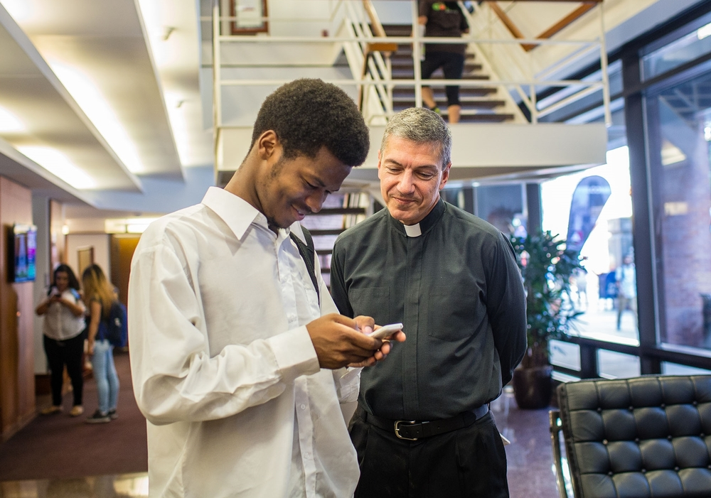 Rev. Stephen Katsouros, S.J., dean and executive director of Arrupe College, helps a student during the first day of classes (Photo by Natalie Battaglia).
