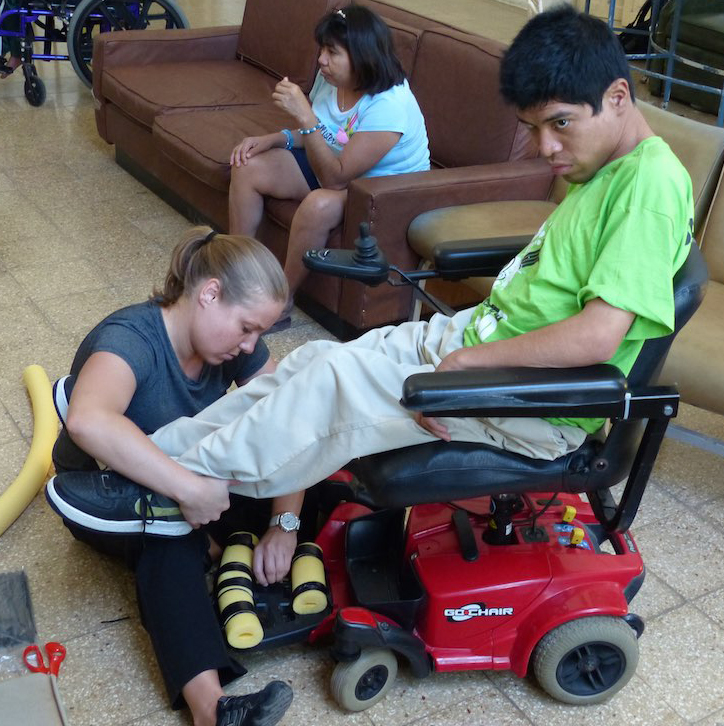 Above: A handicapped man from Merida gets physical therapy instructions from Wheeling Jesuit University student Christy Shaneyfelt. (Photo courtesy of Wheeling Jesuit University)
