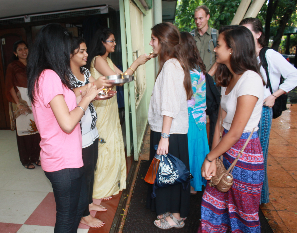 Santa Clara University students being welcomed by students at Xavier Institute of Engineering, Mumbai, in an Indian tradition of pasting sandalwood paste on their forehead and throwing flower petals. (Photo courtesy of Santa Clara University)