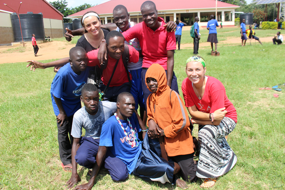 Rockhurst University junior Haley Mathews, top left, and 2014 Rockhurst graduate Melissa Hopfinger, lower right, pose for a photo with students from Ocer Campion Jesuit College in Gulu, Uganda. (Photo courtesy of Rockhurst University)