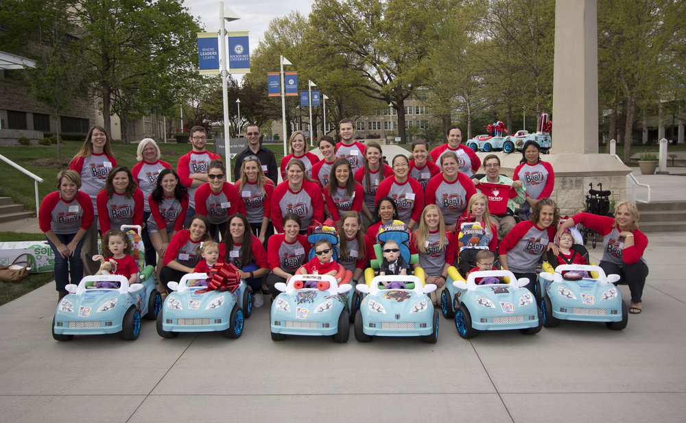 Volunteers with Variety KC GoBabyGo! Powered by Rockhurst University pose with children receiving their new mobility vehicles at an April 2016 event on the University campus (Photo by Rockhurst University)