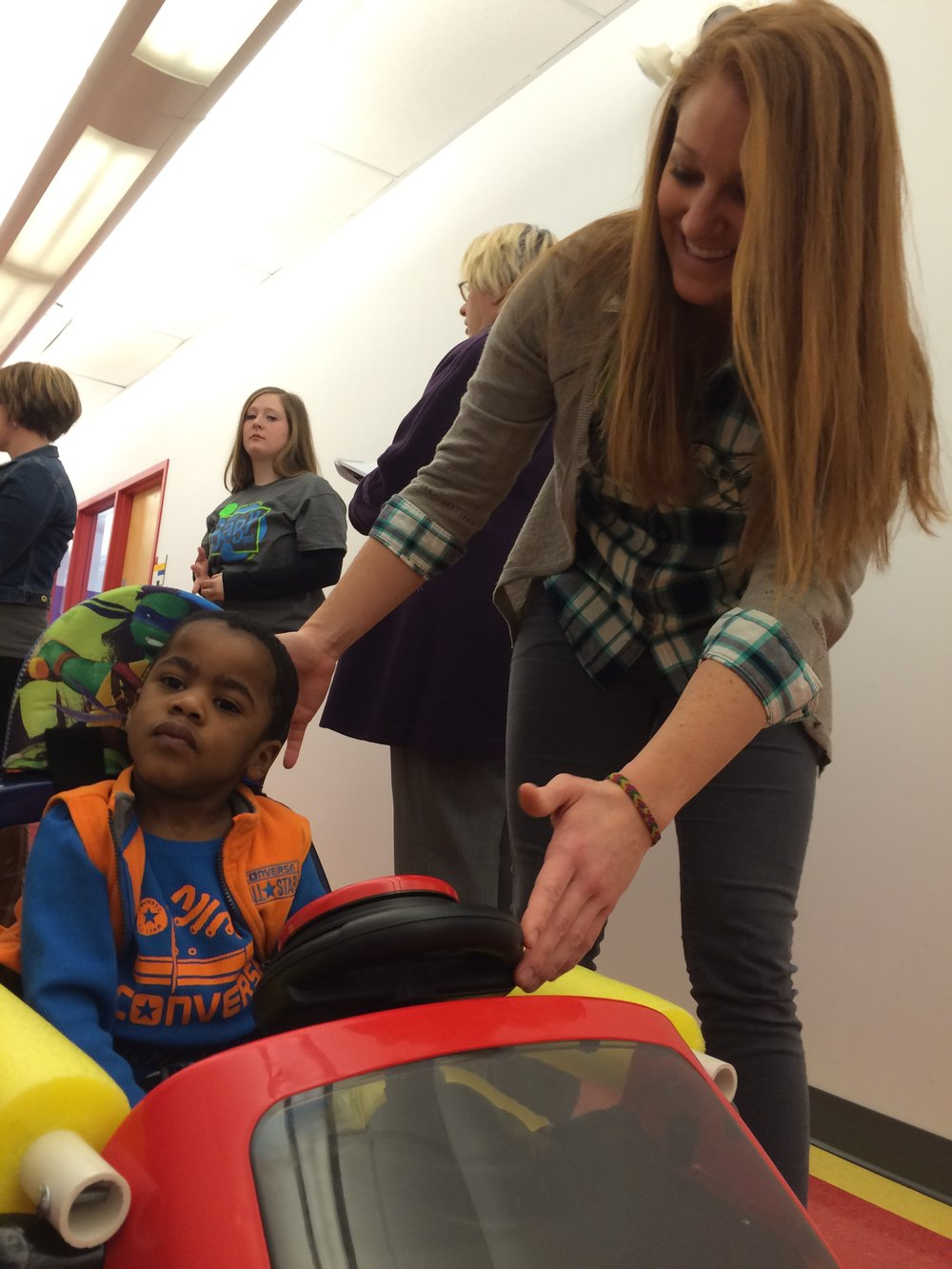 Trace Bales test drives his GoBabyGo! car with help from Rockhurst University physical therapy student Mallory White in March 2015 at the Children's Center for the Visually Impaired in Kansas City, MO. (Photo by Rockhurst University)