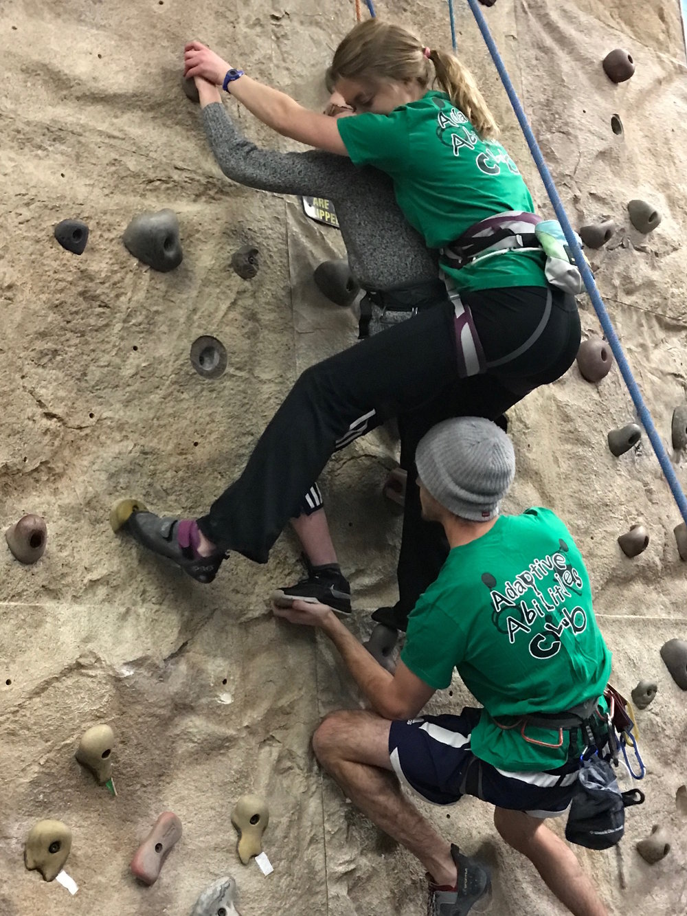 Adaptive Abilities Club members Kelly Bush and Zach Hodgson help Matthew Knowles rock climb (Photo by Marquette University)