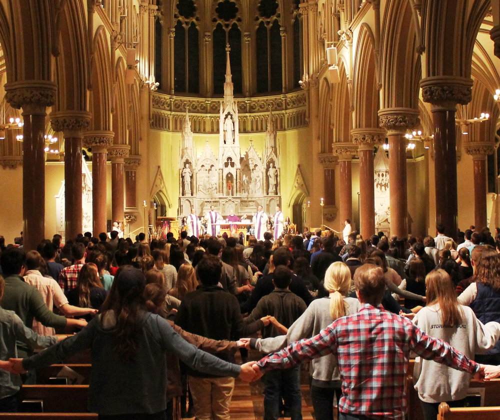 Students hold hands across aisles while saying the Lord's Prayer at College Church during the 9 PM Mass (photo by Molly Daily for Saint Louis University)