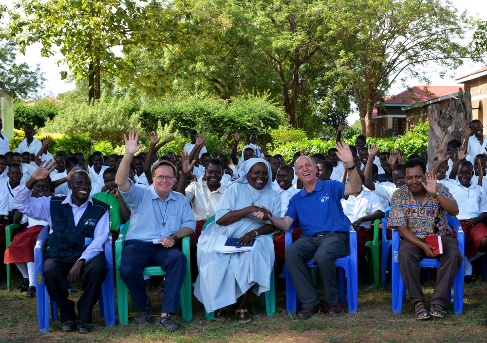 JRS International Director, Rev. Thomas H. Smolich S.J. (in dark blue), visiting St. Mary Assumpta in uganda, where JRS provides scholarships, teacher training & school supplies (photo by JRS International)