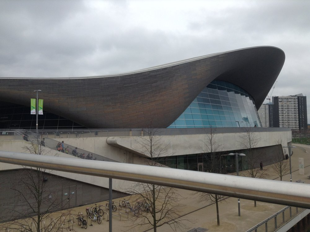 "2:40  Nightswimming  Onto the London Aquatics Centre which is another amazing building, inside and out. There was a student competition on so no photos from inside though. Lovely toilets!     3:30 Hit the road Jack.  On the bus and just organising for leaving. Go!     4:45 Der Der Der Cambridge!  We're on a grand tour of the East of England, and sat/ sitting in a jam just outside Cambridge in the fens..."" oooh, what a big sky etc"". Still a good way off the tea stop."