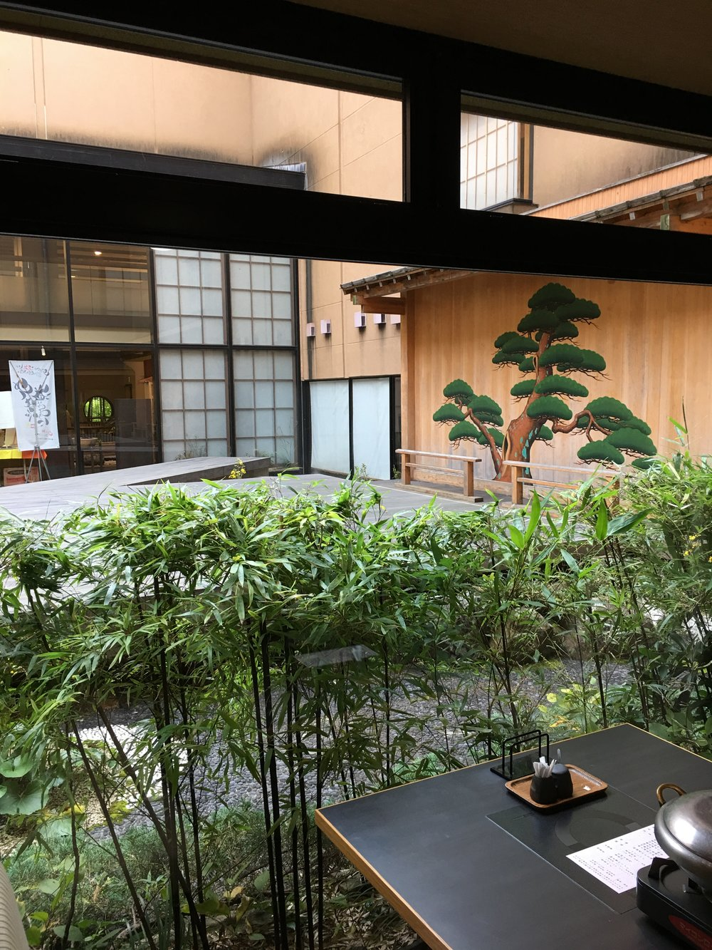 The restaurant presents itself with settings from both modern and traditional styles of Japanese display. Edo-like fashioned Japanese black pine is painted on the smooth wooden surface beyond the transparent glass wall. More of the restaurant table and the left side of the open area view beyond the glass barrier photo is shown:   here  .