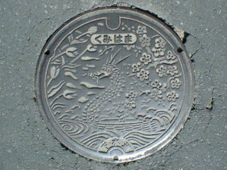 The archaic-appearing manhole in Kumihama, a town in Kyoto Perfecture, perhaps  accredited  by the  Damyojin Cape , resembling that of a dragon soaring on the sea-surface at a certain angle. Legend has it that the avatar of a dragon lives in this area. 「Photo by: Flickr@OKFoundryCompany」