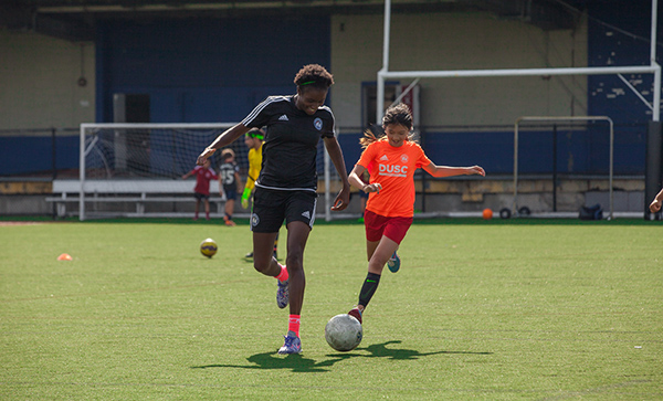 Coach Oumou Toure playing at DUSC Summer Camp.