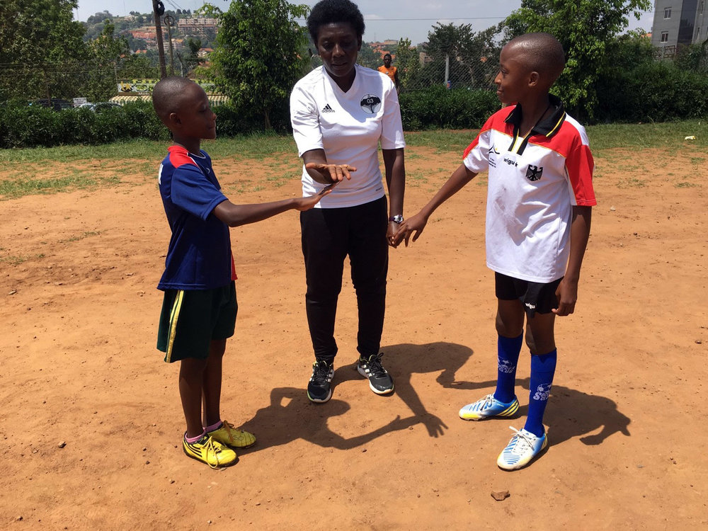Majidah Nantanda conducting the pre-game coin toss with players wearing jerseys and gear donated by clubs in the US.