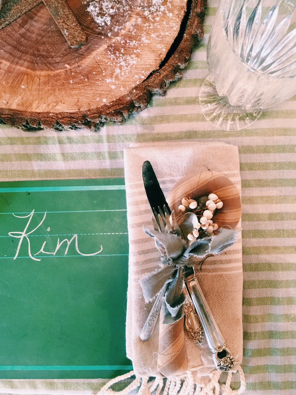 We used turkish towels as a table runner & for our napkins to add texture to the mix. Our friend Jason Counts (of DIRT) handmade the cloth candy cane from vintage ticking. It tied the setting + silverware together in a cool way!