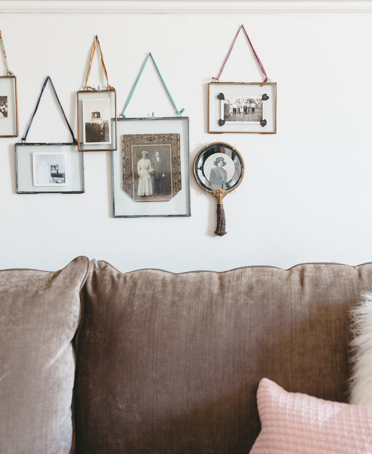 Layered picture frames filled with antique pictures are hung behind the cozy sofa in the bridal suite at the McConnell house | Interior Design: Kim Leggett, owner of City Farmhouse