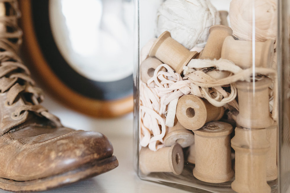 Vintage wooden spools in a glass jar in the bridal suite at the McConnell House | Interior design: Kim Leggett, owner of City Farmhouse