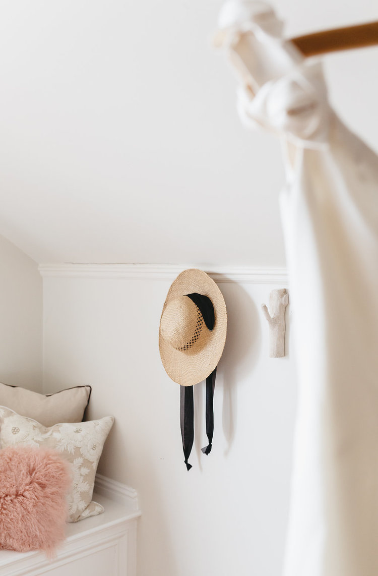 A sun hat hangs on one wall in the bridal suite at the McConnell House | Interior design: Kim Leggett, owner of City Farmhouse