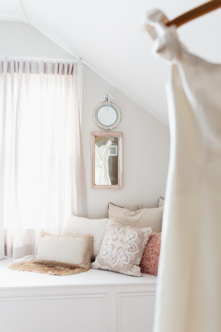 A charming window bench with fun pillows at in the Bridal Suite at the McConnell house | Interior Design: Kim Leggett, owner of City Farmhouse