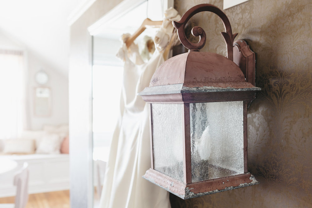 Antique lantern hangs from the wall in the bridal suite at the McConnell House | Interior design: Kim Leggett, owner of City Farmhouse