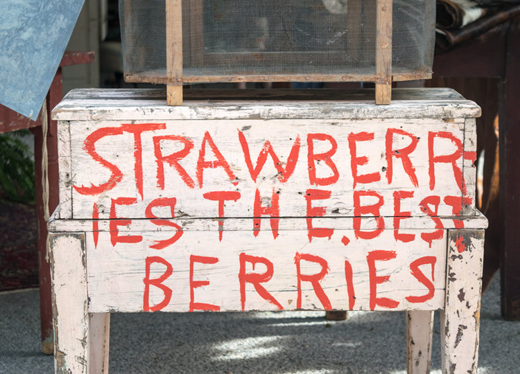 "An adorable vintage produce desk reading ""Strawberries the best berries"" at the City Farmhouse Pop Up Fair 