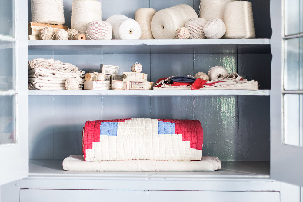 Balls of twine and a red and blue patched quilt at Homestead Manor | Interior Design: Kim Leggett | Photographer: Alyssa Rosenheck