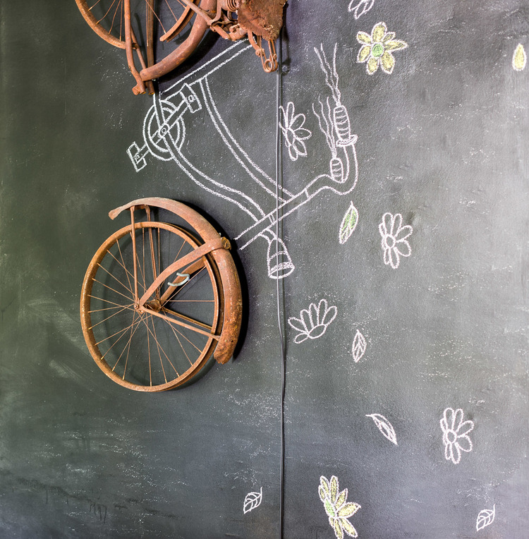 Old rusted bicycle wheels with a hand drawn bicycle using chalk hang from the wall at Homestead Manor | Interior Design: Kim Leggett | Photographer: Alyssa Rosenheck