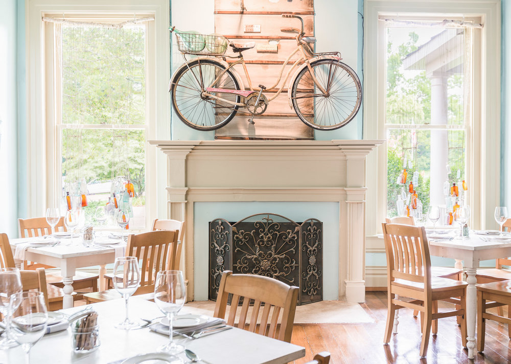 A charming bright dining room with a vintage bicycle hanging on a mantle | Interior Design: Kim Leggett | Photographer: Alyssa Rosenheck