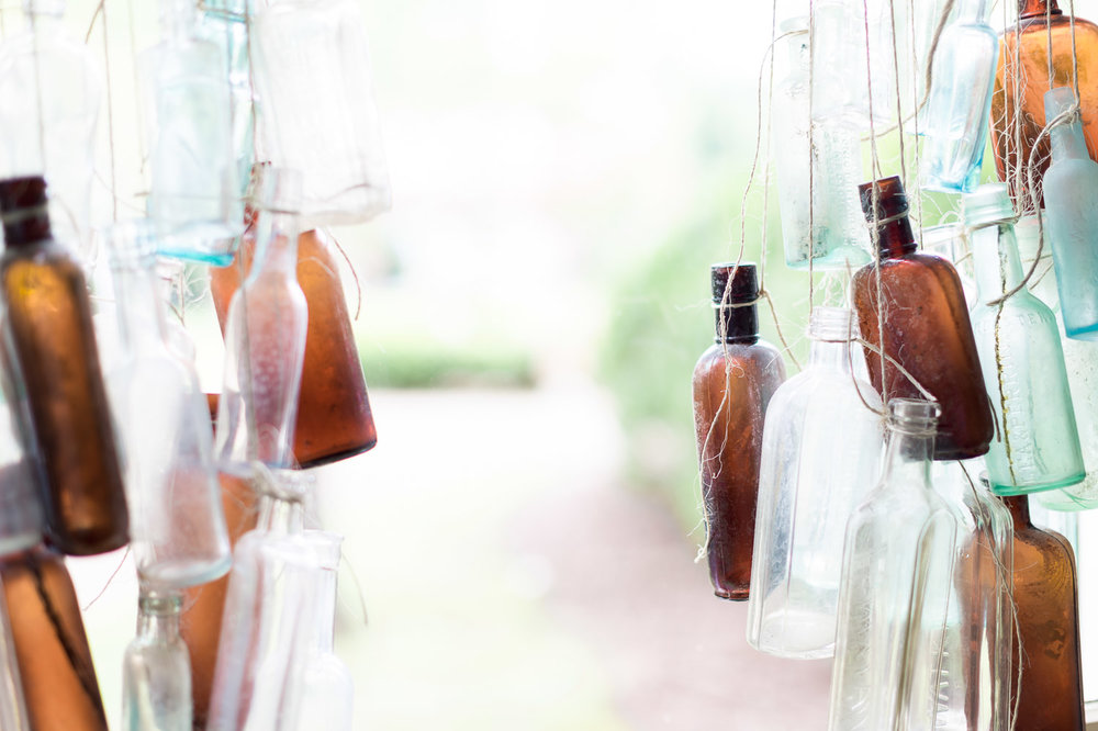 Vintage glass bottles hang from twine at Homestead Manor | Interior Design: Kim Leggett | Photographer: Alyssa Rosenheck