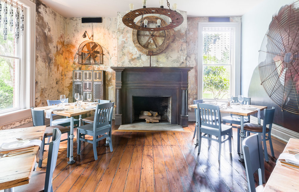 A rustic dining area with blue chairs at Homestead Manor | Interior Design: Kim Leggett | Photographer: Alyssa Rosenheck