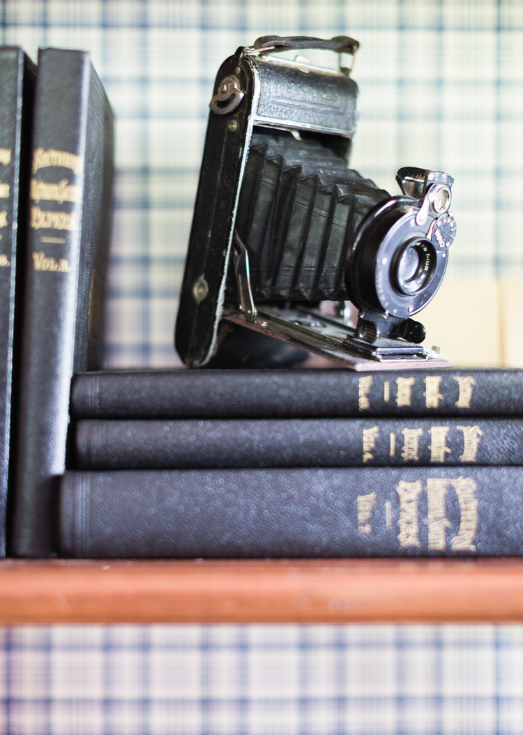 Antique camera on a shelf at Homestead Manor | Interior Design: Kim Leggett | Photographer: Alyssa Rosenheck