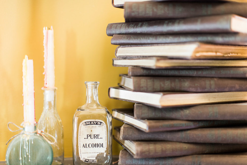 A stack of vintage books at Homestead Manor | Interior Design: Kim Leggett | Photographer: Alyssa Rosenheck