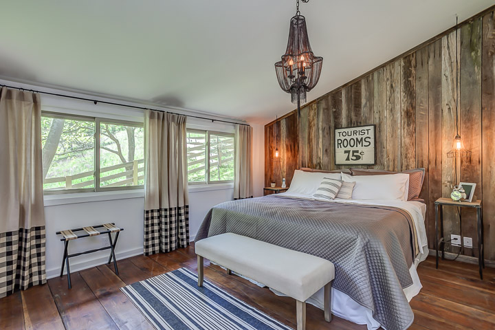 Wood planks installed vertically add a rustic charm to the wall at the Nest | Interior Designer: Kim Leggett