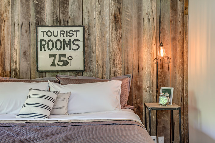 """Tourist Rooms 75 cents"" sign hangs in the bedroom at the Nest 