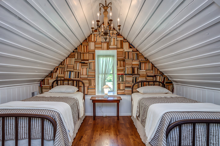 Antique and vintage book cover an entire wall in the bedroom at The Nest | Interior Designer: Kim Leggett