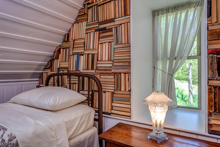 Vintage books make up an elaborate wall treatment at The Nest | Interior Designer: Kim Leggett