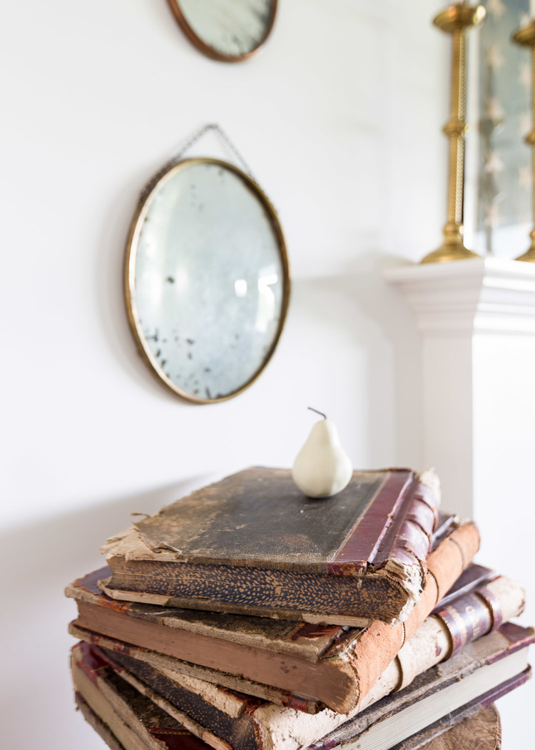 A vintage round mirror and antique book accent the space at One King's Lane | Photography: Alyssa Rosenheck | Interior Design: Kim Leggett