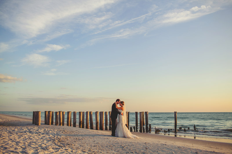 naples backyard beach wedding: bride and groom embracing on beach