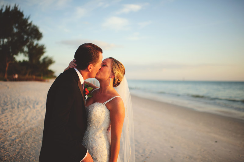 naples backyard beach wedding: bride and groom kissing on the beach