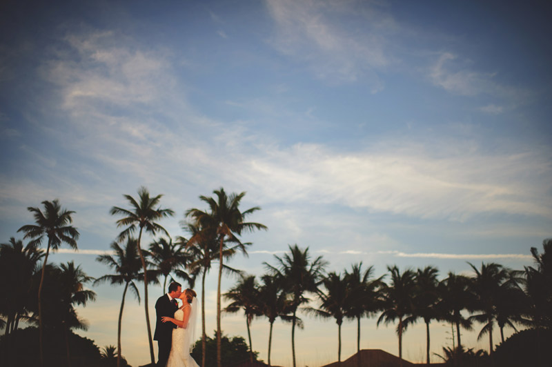 naples backyard beach wedding: groom and bride with palm trees