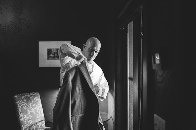 romantic sundy house wedding: groom putting on jacket