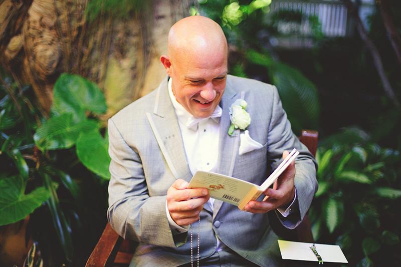romantic sundy house wedding: groom reading his card