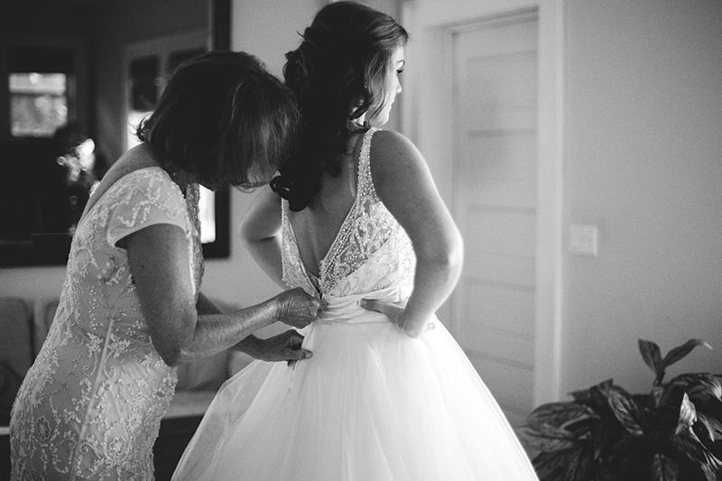 romantic sundy house wedding: mom zipping up dress