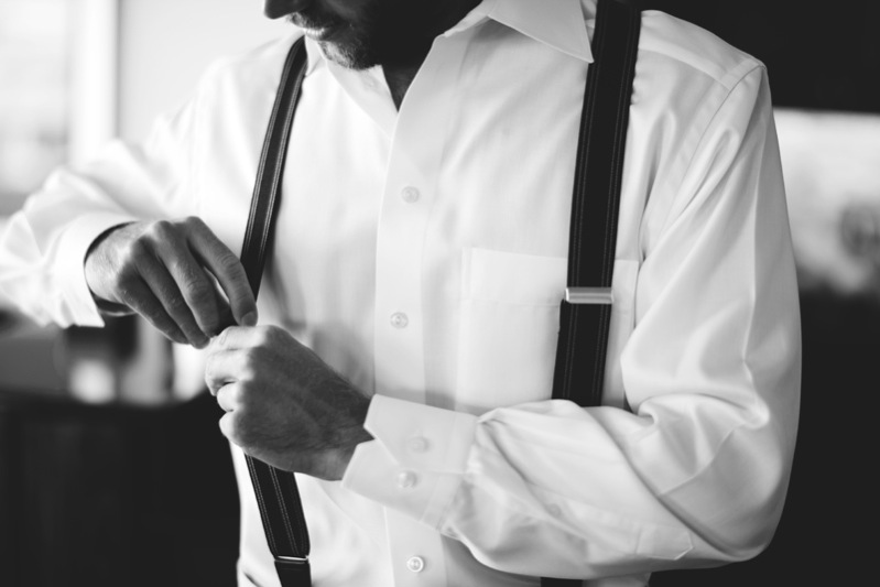 boho backyard wedding naples: groom putting on suspenders