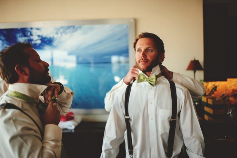 boho backyard wedding naples: putting on bow tie
