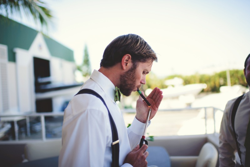 boho backyard wedding naples: groom smoking a cigar