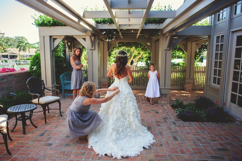 boho backyard wedding naples: bride getting into her dress