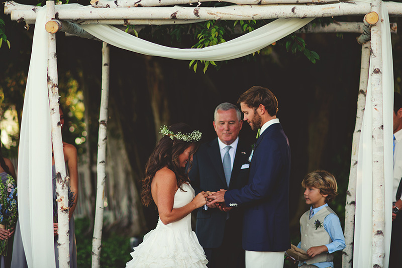 boho backyard wedding naples: bride putting ring on grooms finger