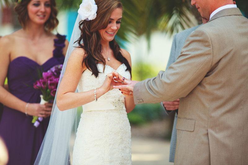 postcard inn holiday isles wedding: bride putting ring on groom