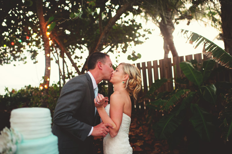 siesta key backyard wedding: cake cutting kiss