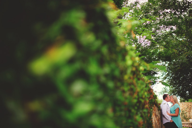 bella collina engagement session: kissing along ivy wall