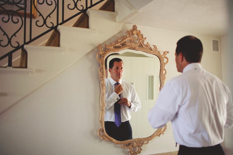 naples backyard beach wedding: groom tying tie