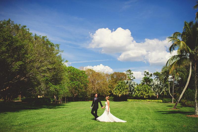 naples backyard beach wedding: bride and groom walking across lawn